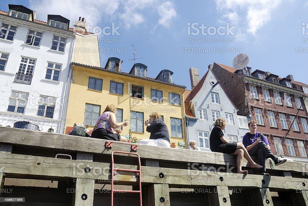 People sitting at the quayside in Nyhavn stock photo