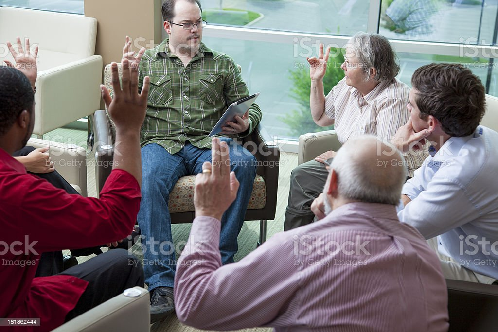People sitting in a cirle and voting by rasing hands stock photo