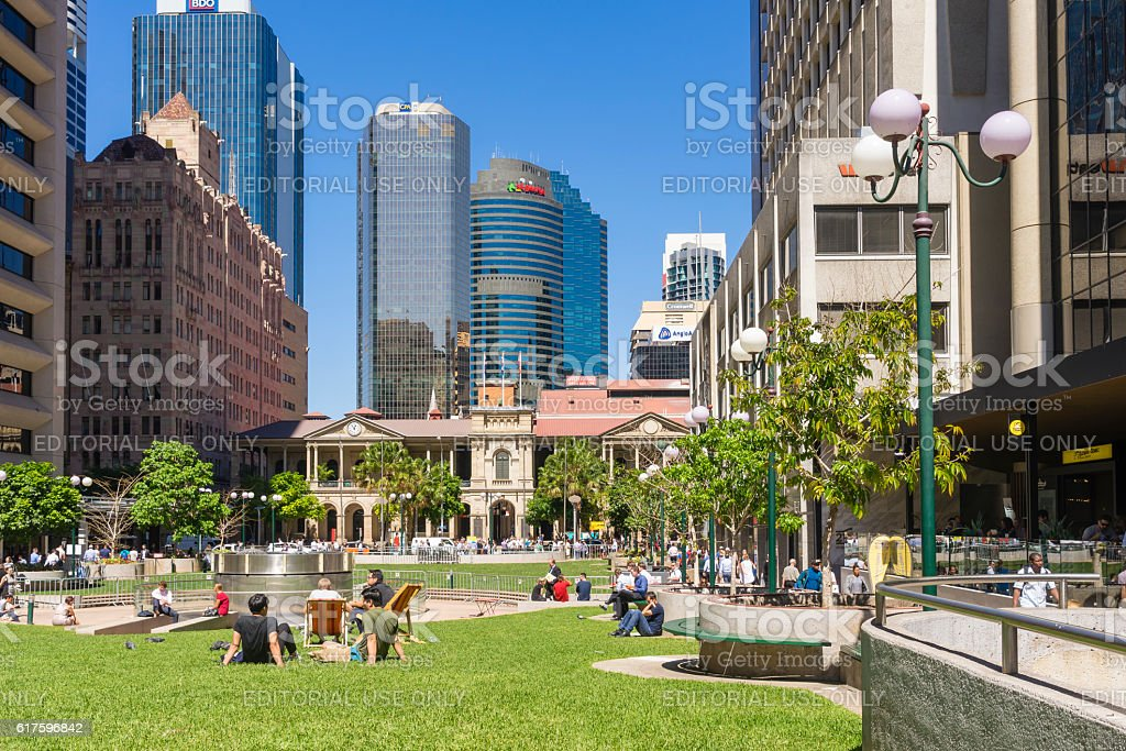 People sitting in the lawn and Brisbane skyline stock photo