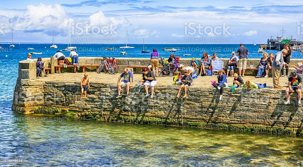 People sitting on the harbor wall breakwater at Swanage, UK stock photo