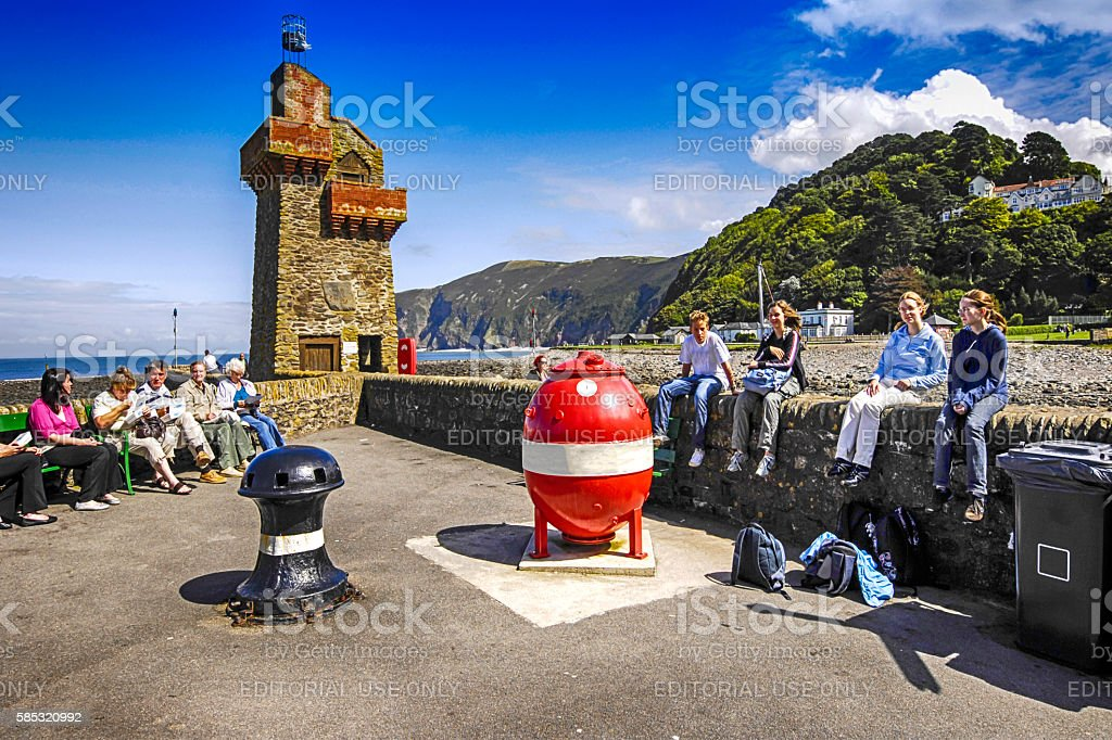 People sitting on the  harbour entrance walls to Lynmouth, UK stock photo