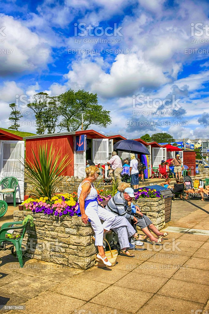 People sitting outside their beach huts at Swanage, UK stock photo