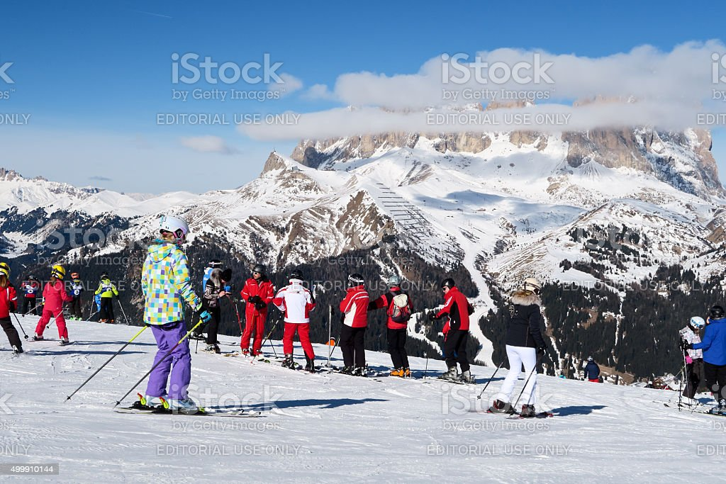 People skiing a cold sunny day in Italian Dolomites. stock photo