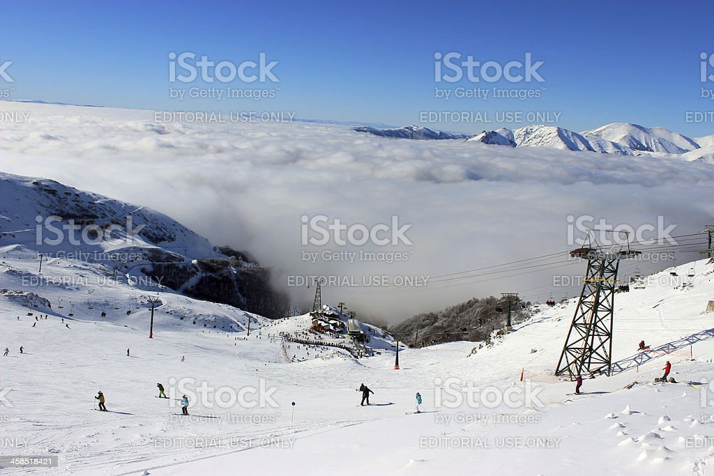 People skiing above the clouds at CERRO CATEDRAL ski station stock photo