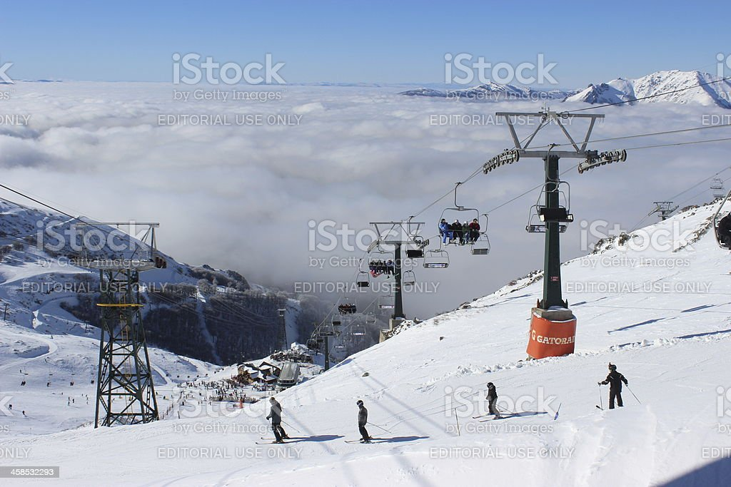 People skiing above the clouds at ski station CERRO CATEDRAL stock photo