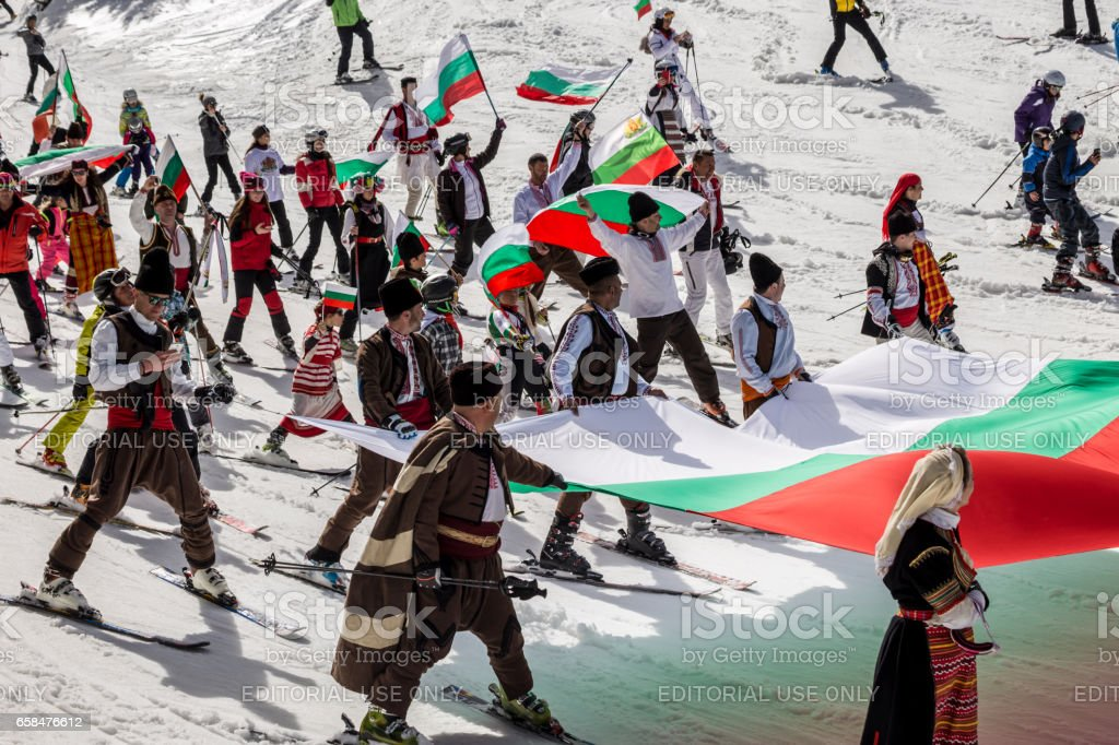 People skiing dressed with traditional bulgarian clothes. stock photo