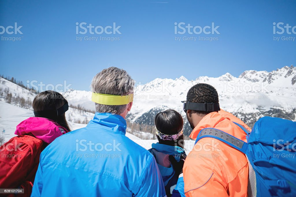 Group of people skiing and looking at the mountains - winter sports