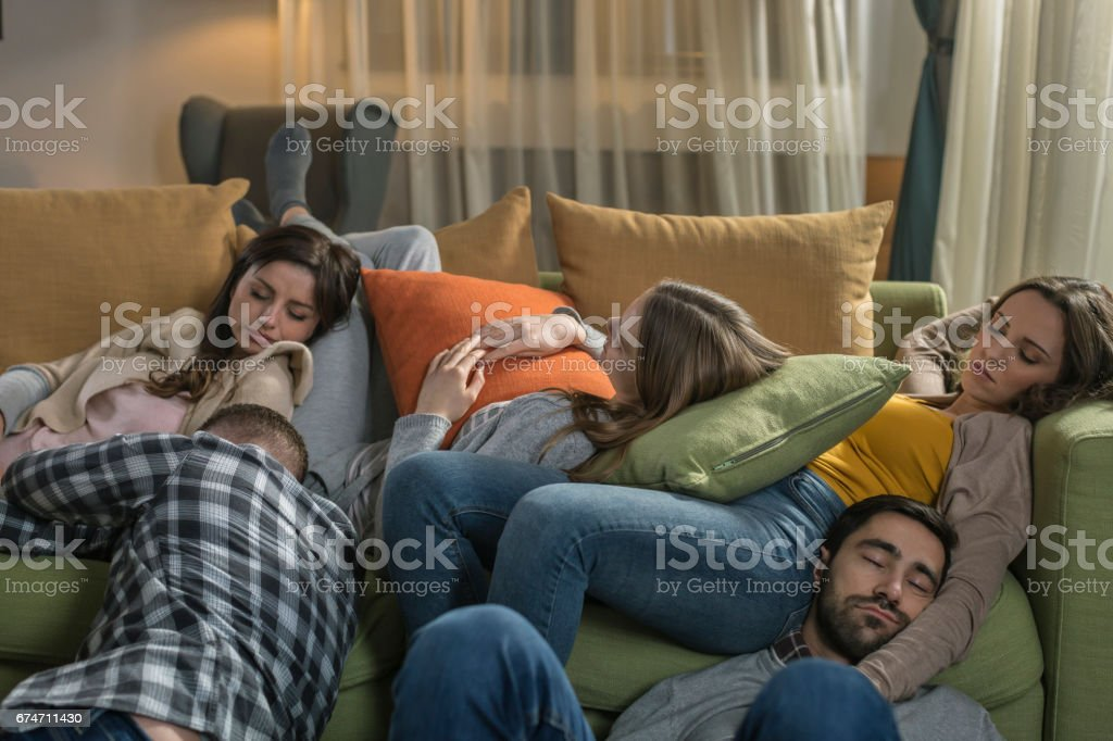 Young people sleeping on sofa and floor after party at home
