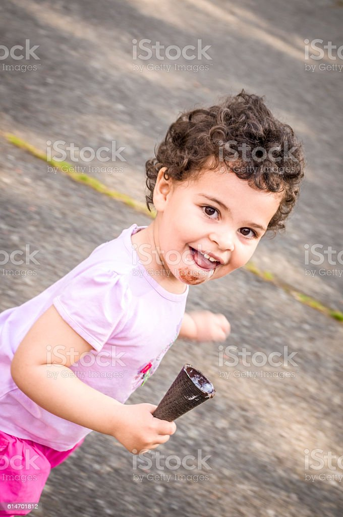 People: Smiling Child (2-3) Running with Ice Cream in Hand stock photo