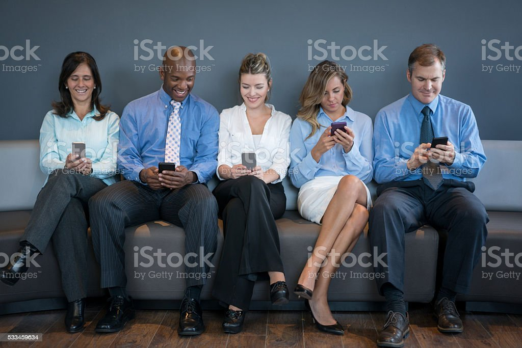 People social networking on their phones at the office stock photo