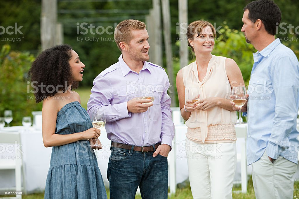 People socialising at outdoor dinner party stock photo