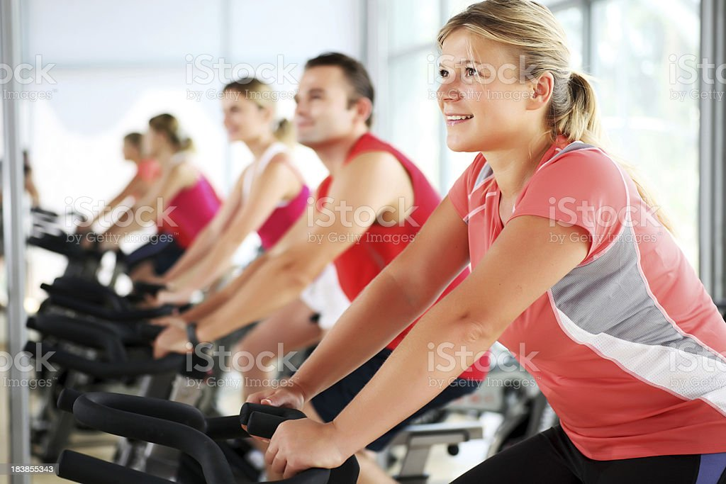 People spinning on bicycles in a modern gym royalty-free stock photo