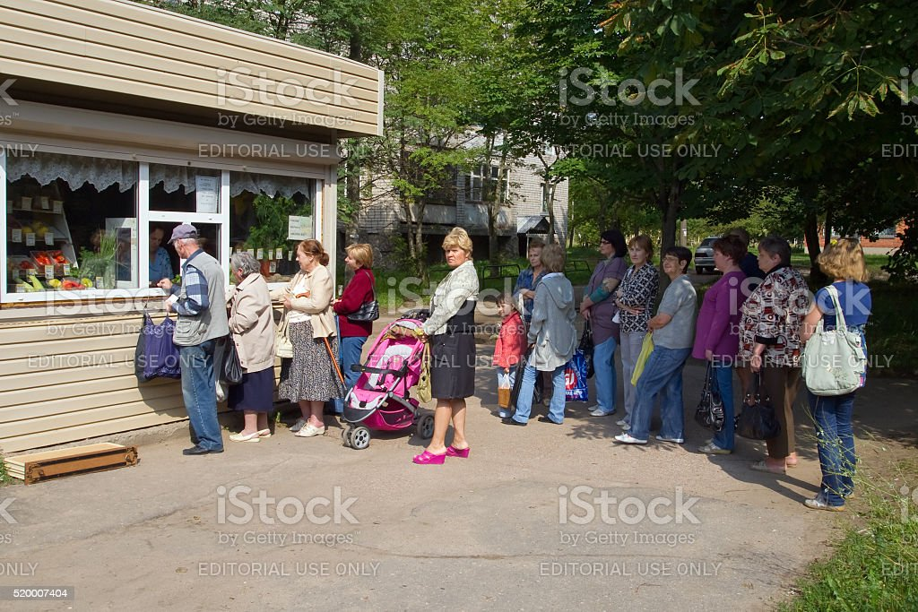 People stand in a queue at the kiosk for food stock photo