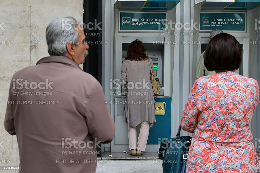 People stand in queue to use the ATMs stock photo