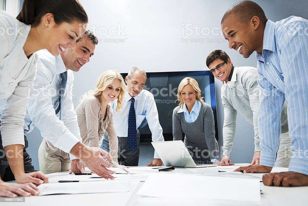 People standing around a table with a laptop stock photo