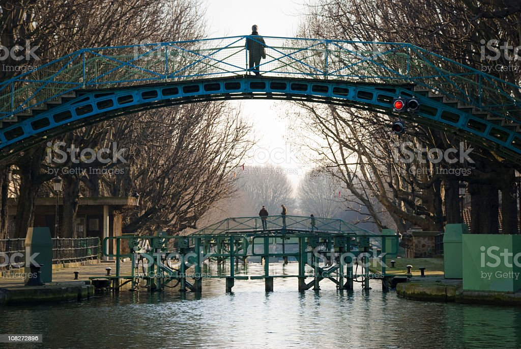 People Standing on Bridge Over Canal Saint Martin in Paris stock photo