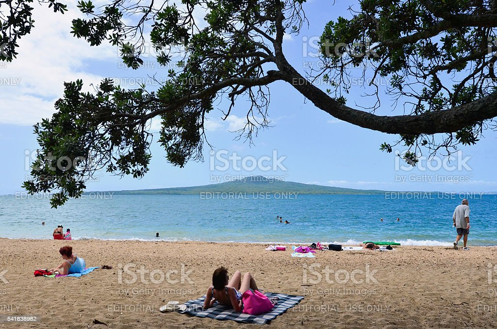 People sunbathing and swimming in Devonport beach Auckland stock photo