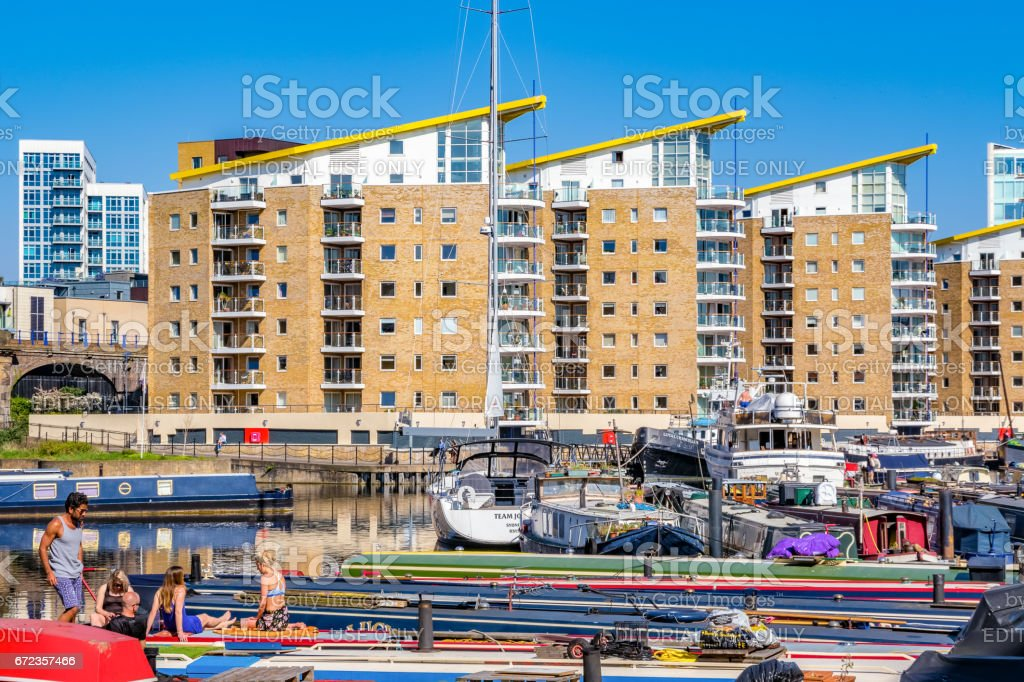 People sunbathing on the boats moored at Limehouse Basin stock photo