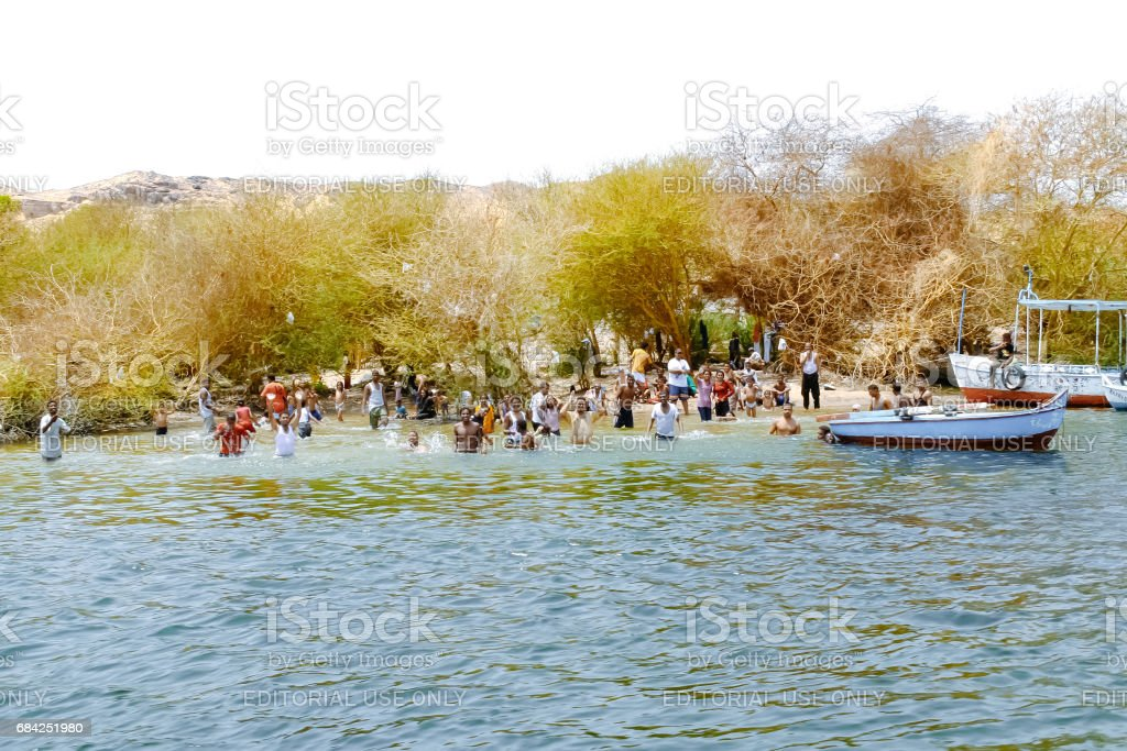 Aswan, Egypt - August 19, 2006: People swim in the Nile river. Aswan, Egypt. Aswan is a busy market and tourist centre located just north of the Aswan Dams on the east bank of the Nile at the first cataract stock photo