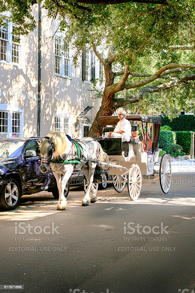 People taking a Horse and Carriage ride around Charleston, SC stock photo