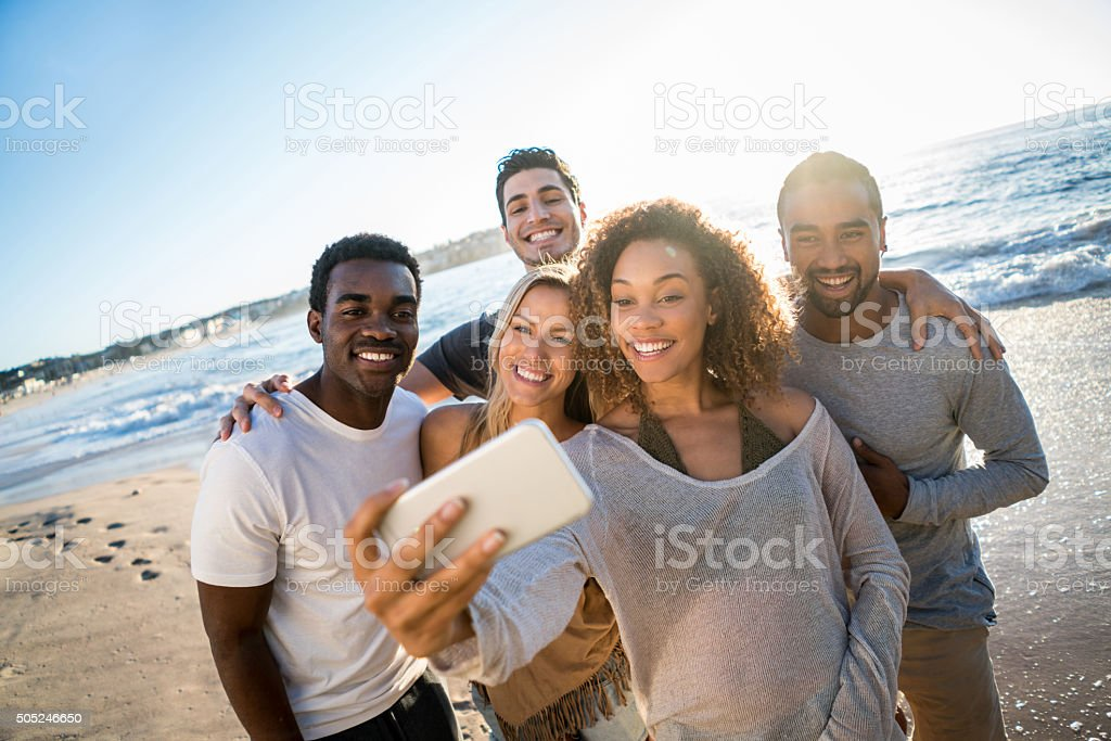 People taking a selfie at the beach stock photo