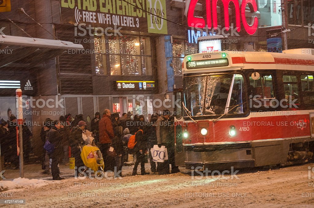 People taking a streetcar in Toronto under heavy snowfall stock photo