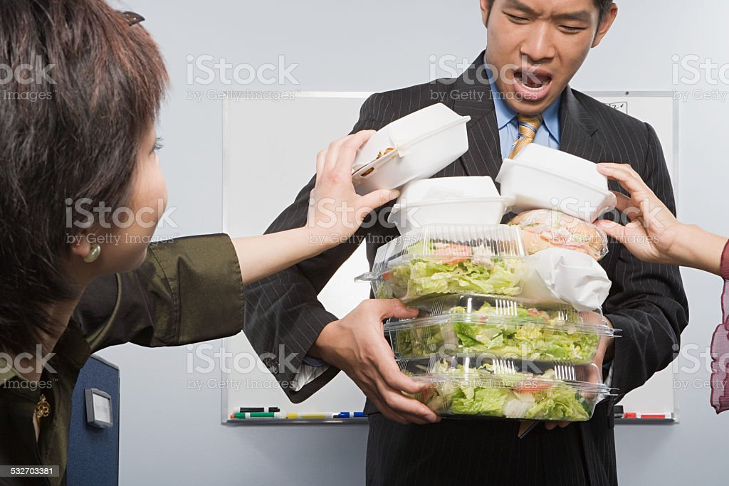 People taking food from colleague stock photo