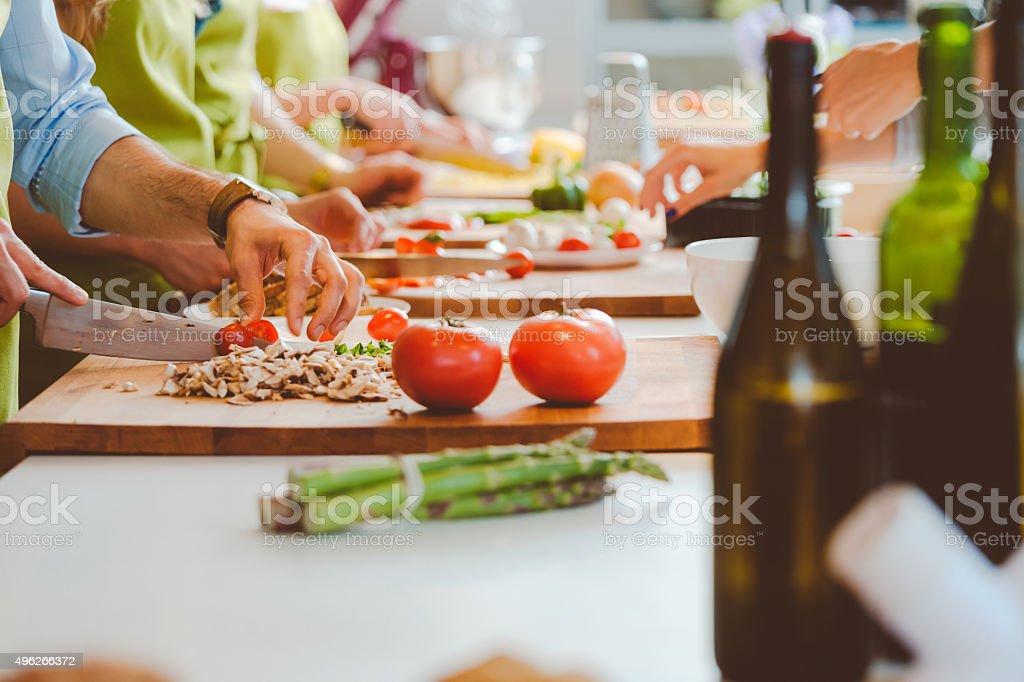 People taking part in cooking class, slicing vegetables stock photo