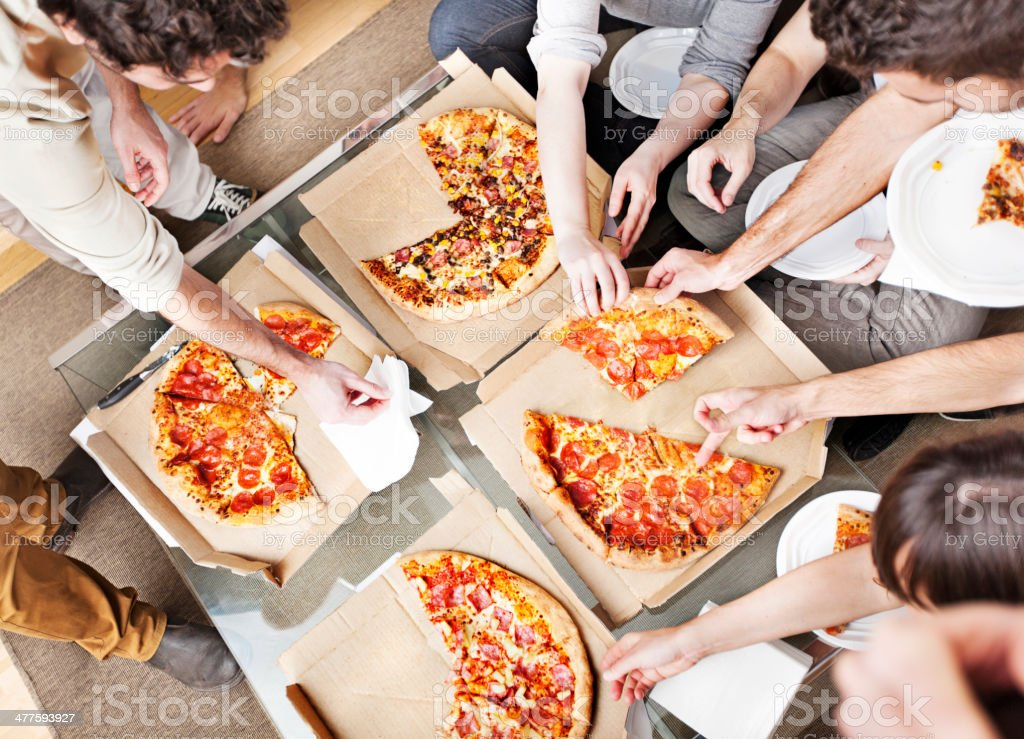 People taking pizza slices stock photo