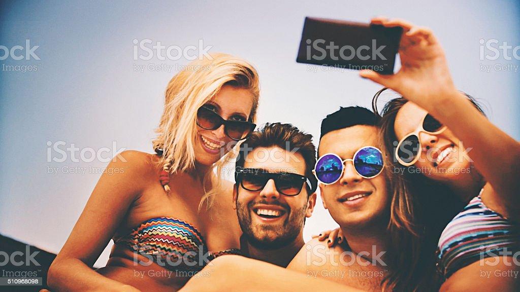 People taking selfies at beach. stock photo