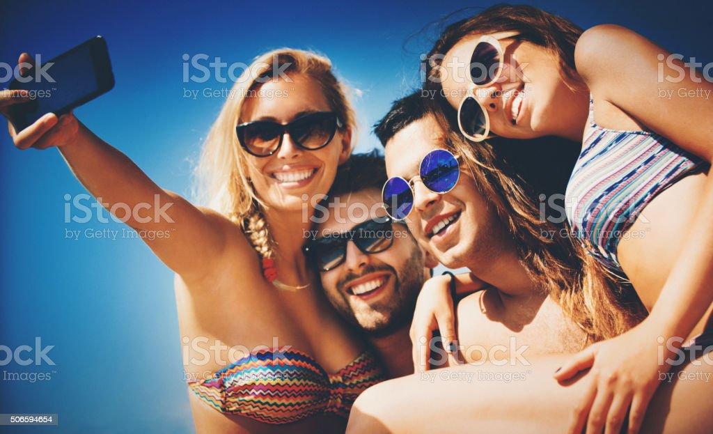 People taking selfies on beach. stock photo