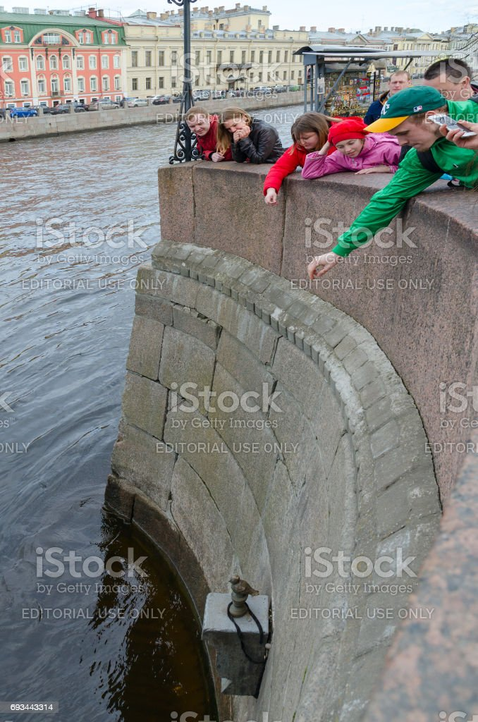People throw coins on pedestal of Chizhik-Pyzhik monument, St. Petersburg, Russia stock photo
