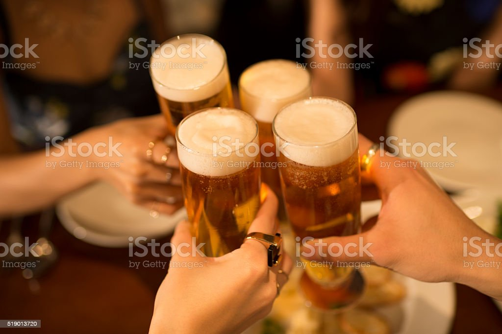 People to the toast with a beer in the tavern stock photo