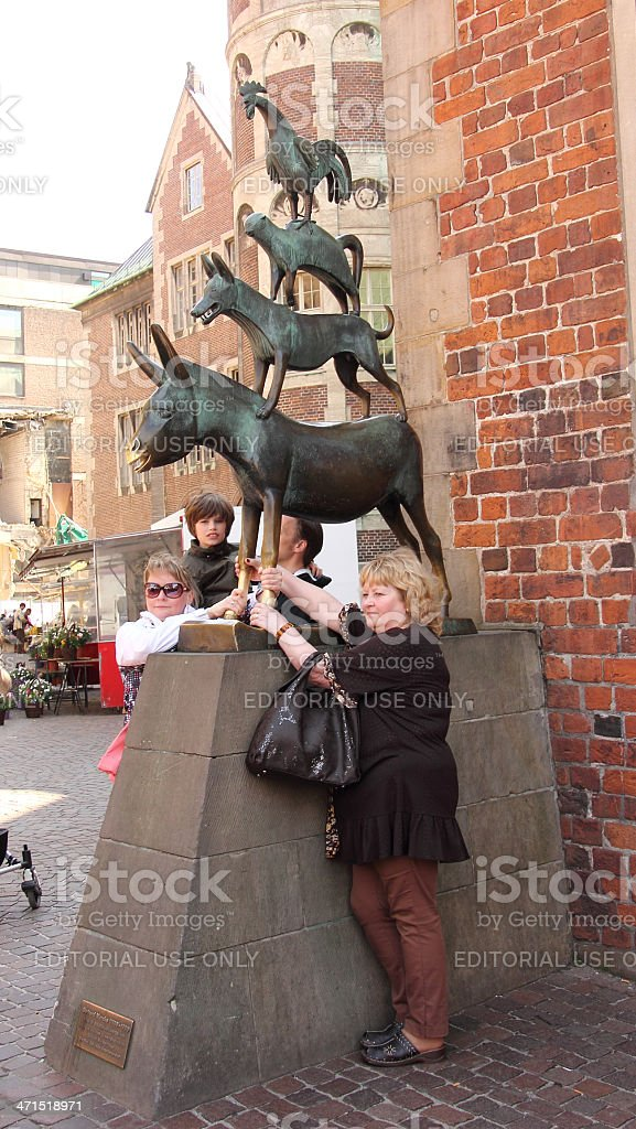 people touching statue of the town musicians_Bremen stock photo