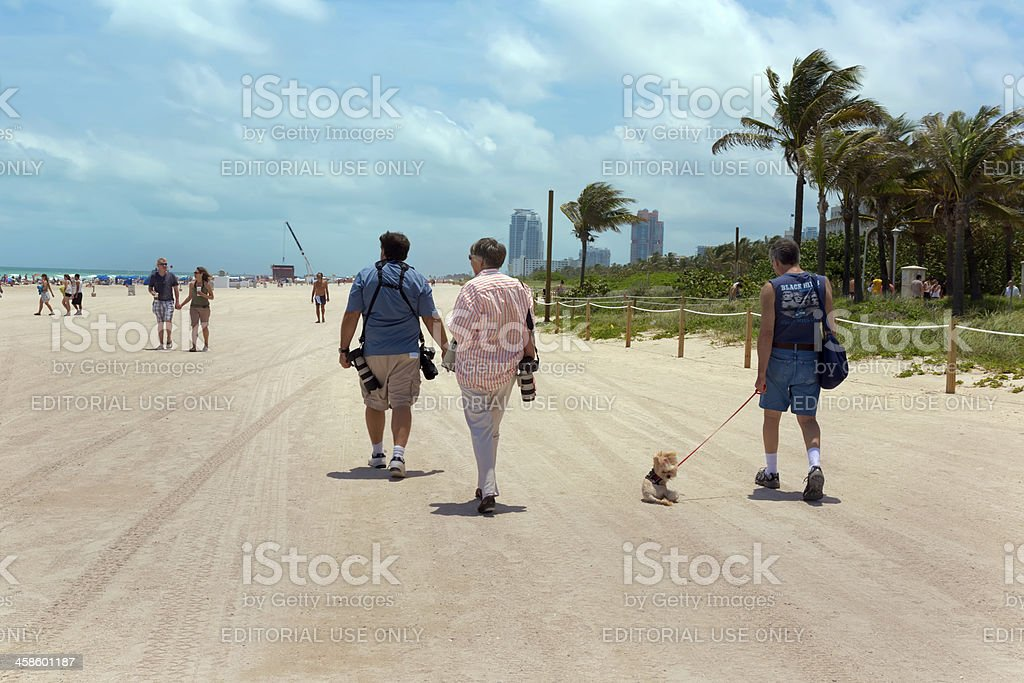 People: Tourists walking on a beach in Florida stock photo