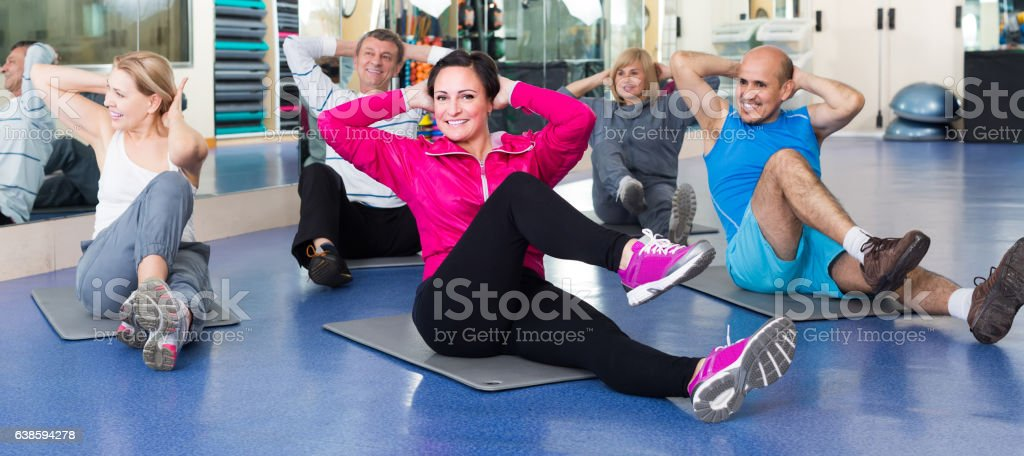 people training in a gym on sport mats stock photo