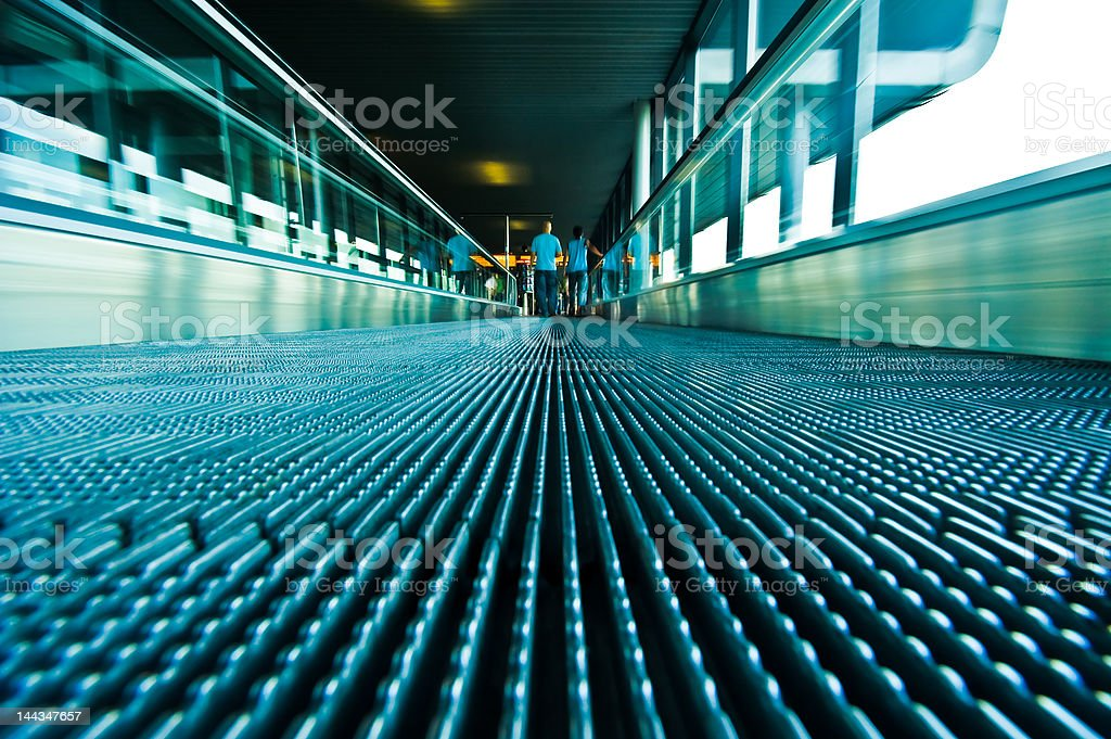 people traveling on a moving escalator royalty-free stock photo
