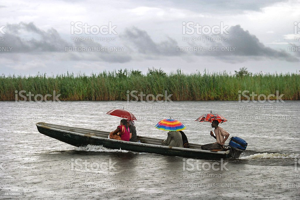People travelling in a canoe during rainfall stock photo