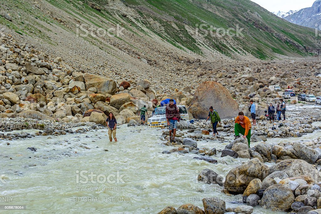 People trying to cross through the flow of glacial waterfall stock photo