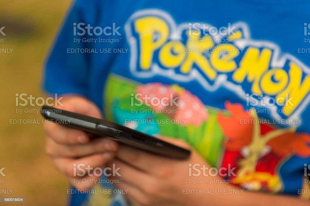 People Use Mobile Phones to Play Game Pokemon Go Outdoors stock photo