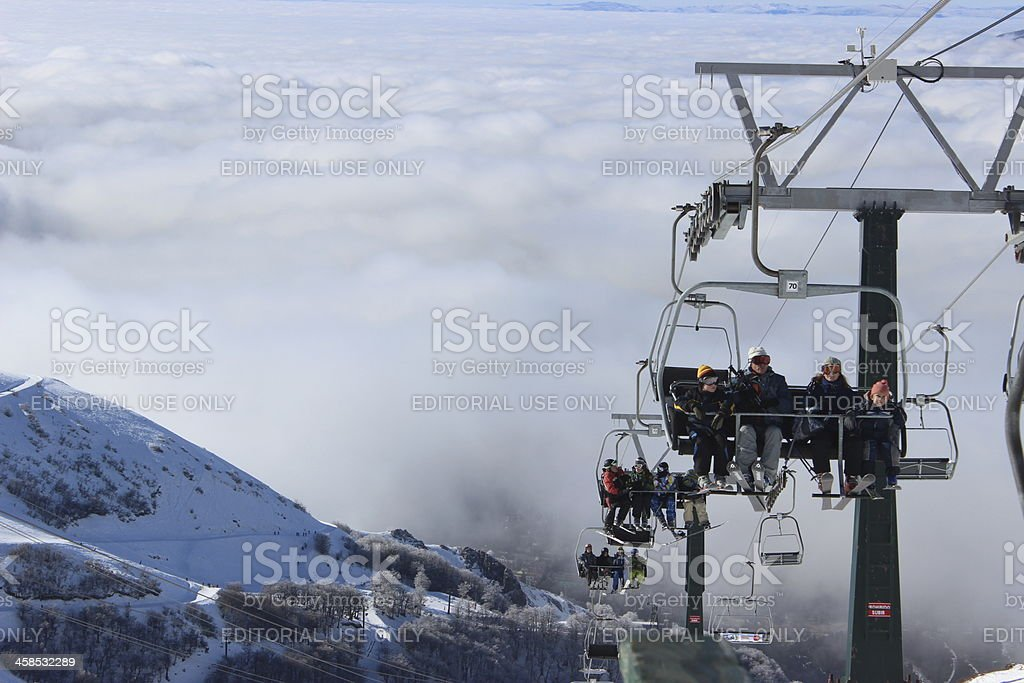 People using chair lifter above the clouds stock photo