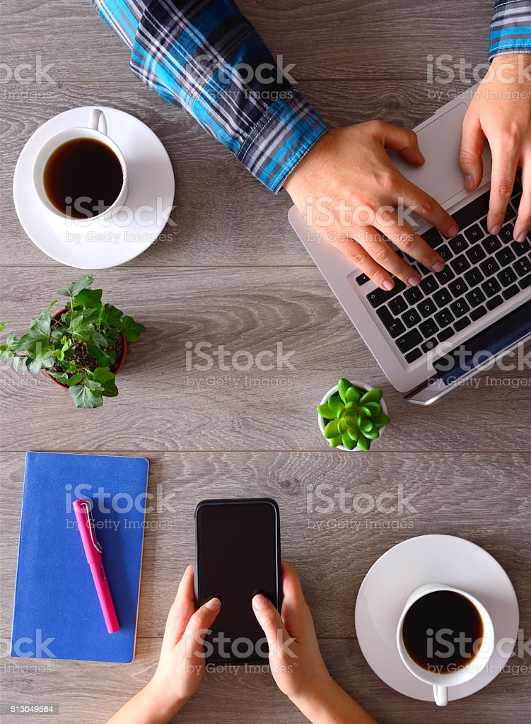 People using smartphone and laptop on desk stock photo