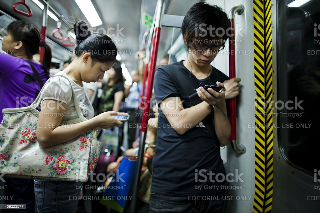 People using smartphones in subway train royalty-free stock photo