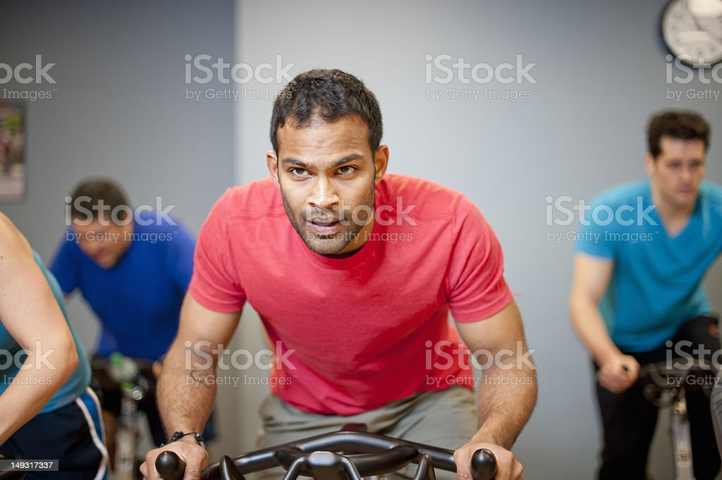 People using spin machines in gym stock photo