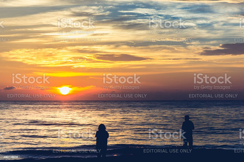 People view the sunrise from the sea. stock photo