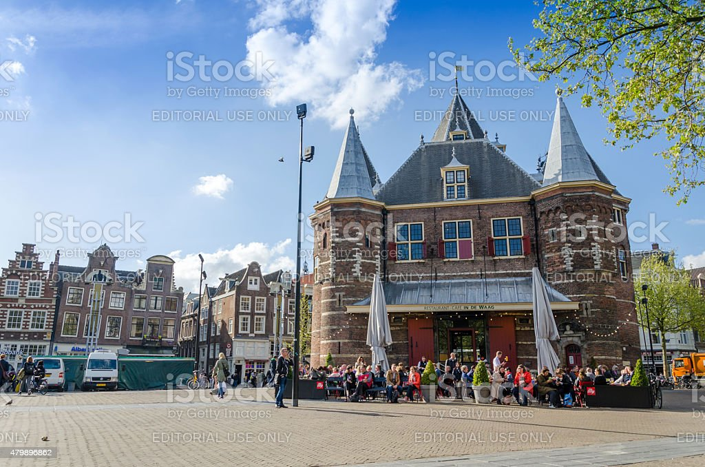People visit The Waag on Nieuwmarkt square in Amsterdam. stock photo
