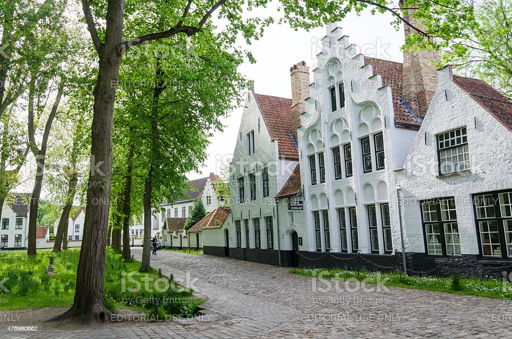 People visit White houses in the Beguinage (Begijnhof) in Bruges. stock photo