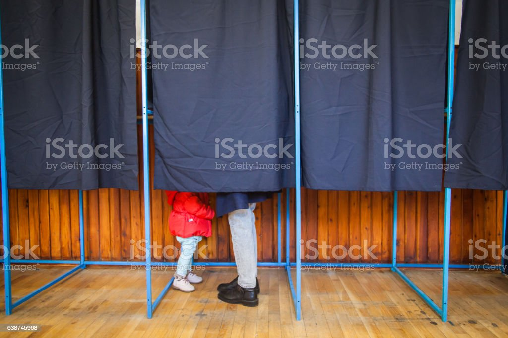 People vote in voting booth stock photo