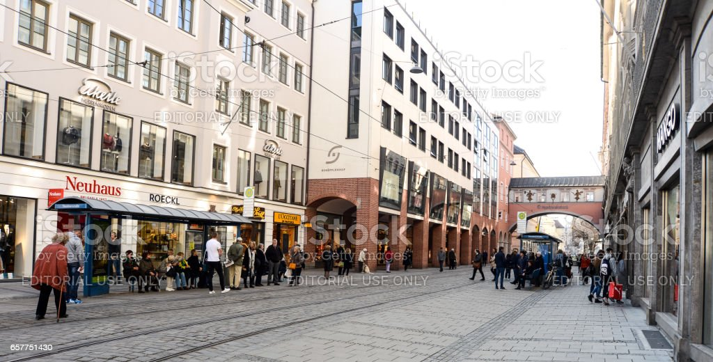 People wait at a streetcar stop for the next streetcar to come stock photo