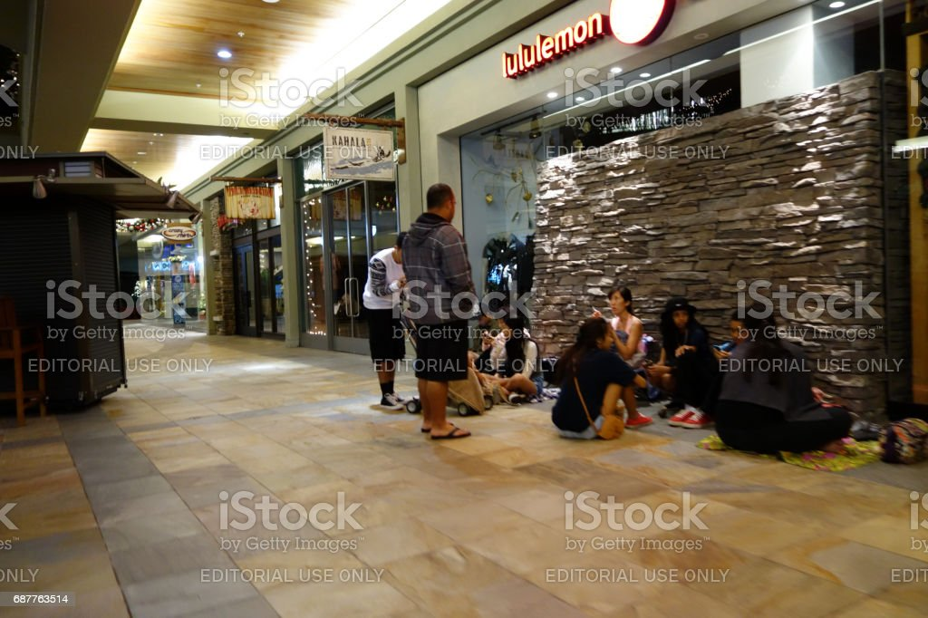 people wait on the floor in line for store opening of Lululemon stock photo